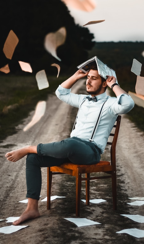 Great storytelling: image of a young man sitting on a chair in a road while sheets of paper rain down on him