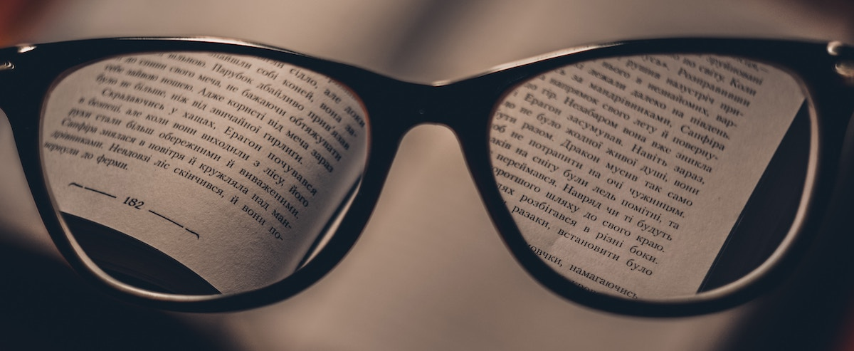 Communicate with a voice actor: image of a pair of glasses focusing on a page