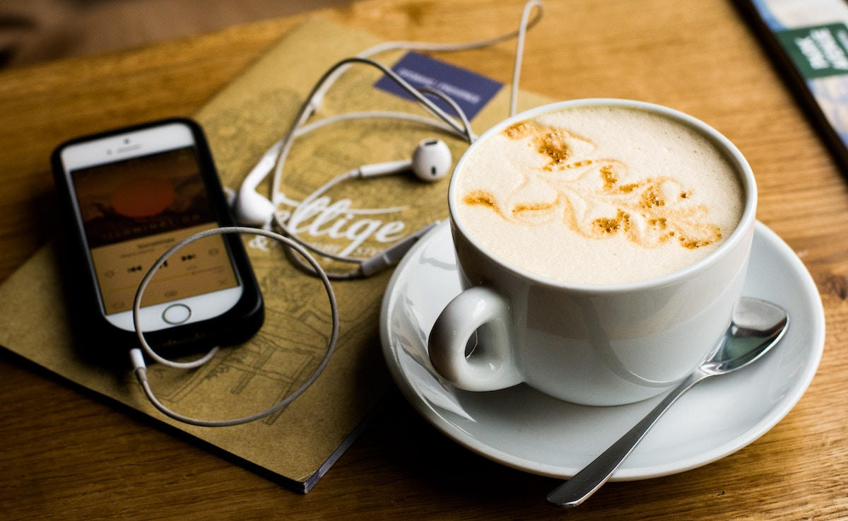 cup of coffee with a mobile phone and EarPods