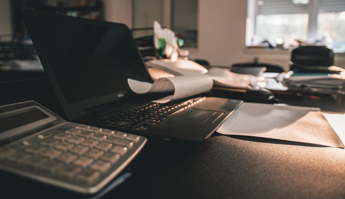 calculator lying next to a laptop computer
