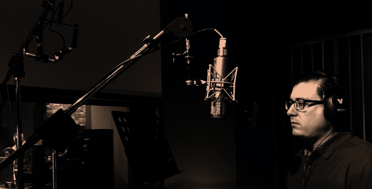 Hiring a voice actor: man standing in front of a studio mic