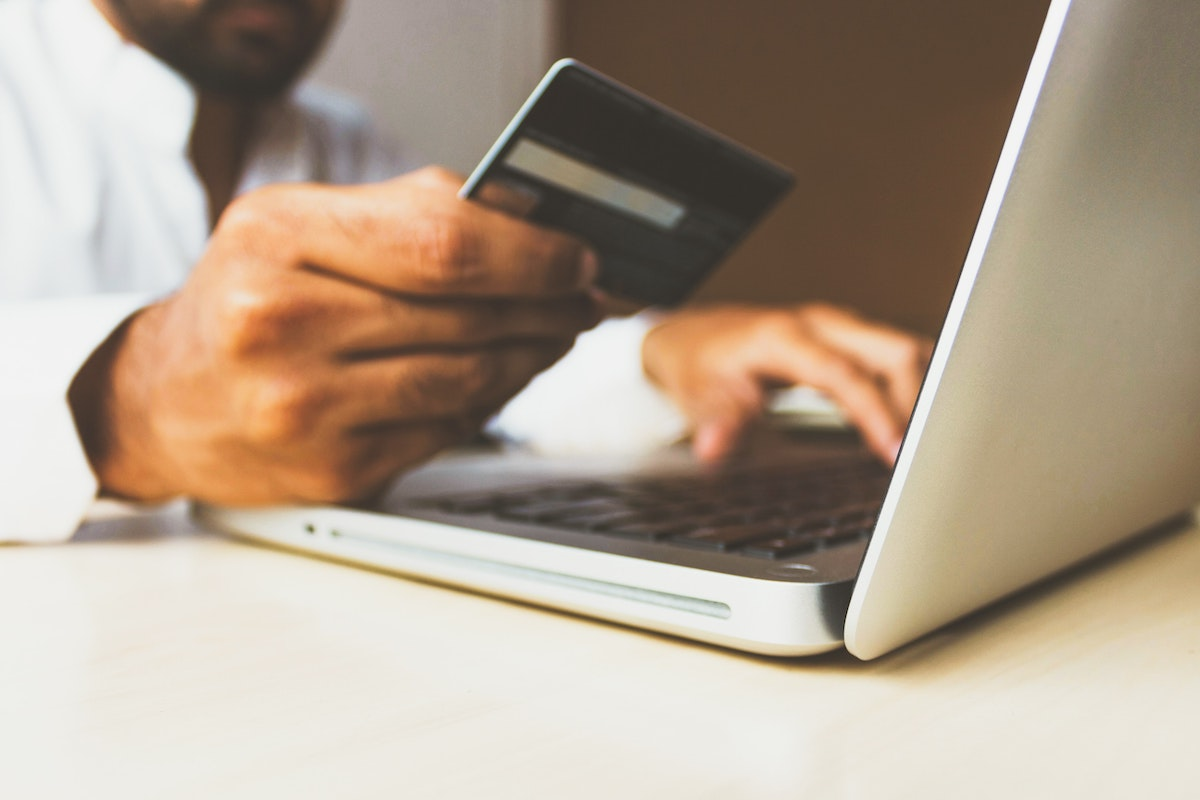 Online platforms vs. booking agencies: man in front of a laptop holding a credit card