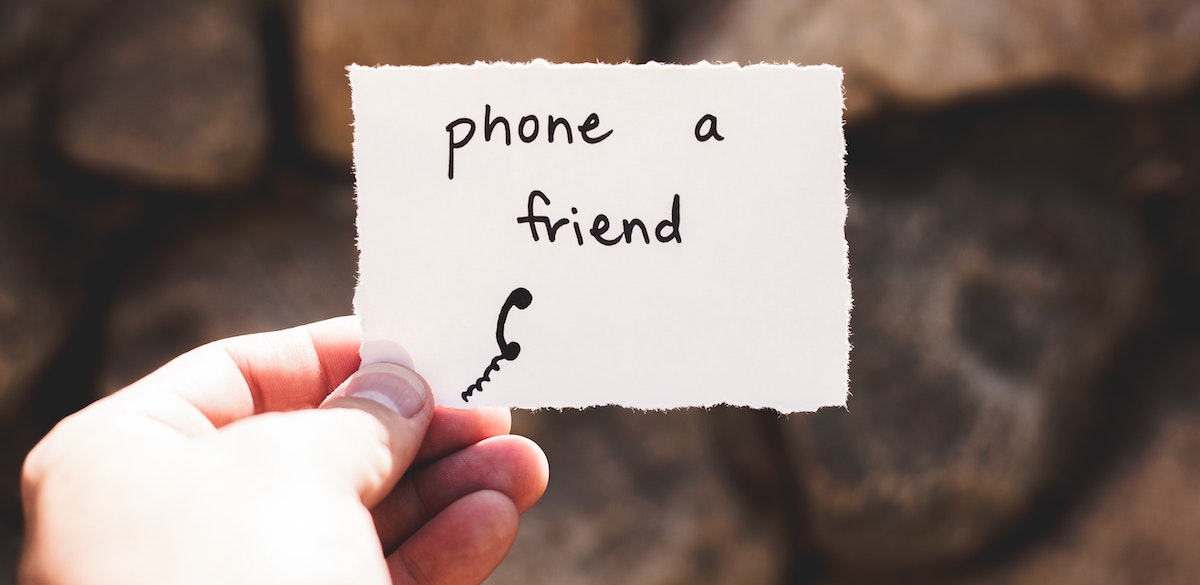 """a hand holding a note that says: """"Phone a friend."""""""