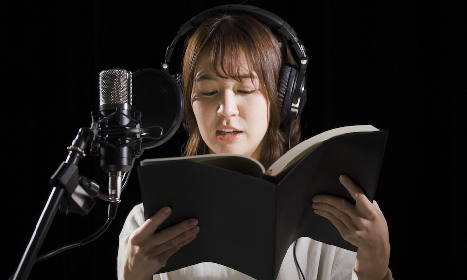 image of young woman reading in front of a mic