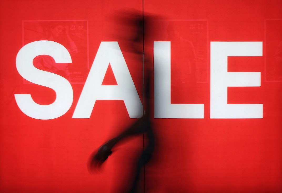 cheap voice overs: man walking past sale sign