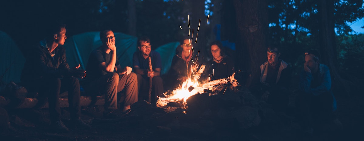 power of a voice over: people sitting around a fire in the dark