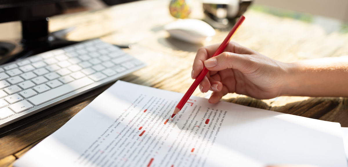 image of a hand holding a pen over a script