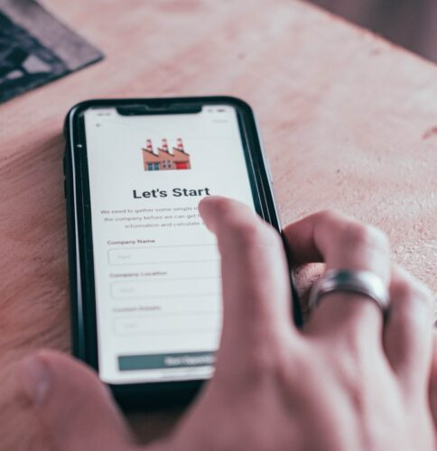 Customer retention tips: image of a man's hand and a online form displayed on a mobile phone