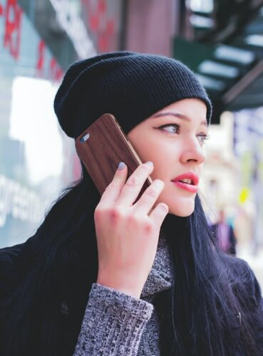 Customer retention tips: image of woman listening to a message on a mobile phone