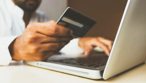 Customer retention tips: image of a man's hands over a laptop holding a credit card