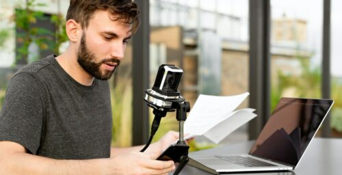 Most out of a voice actor: image of a man sitting with a mic in front of his laptop
