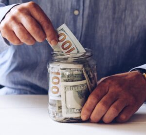 Podcast monetization: image of hands placing paper money into a jar