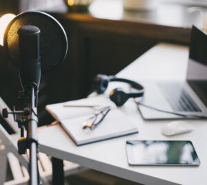 Professional podcast: image of a podcast mic and a laptop on a desk