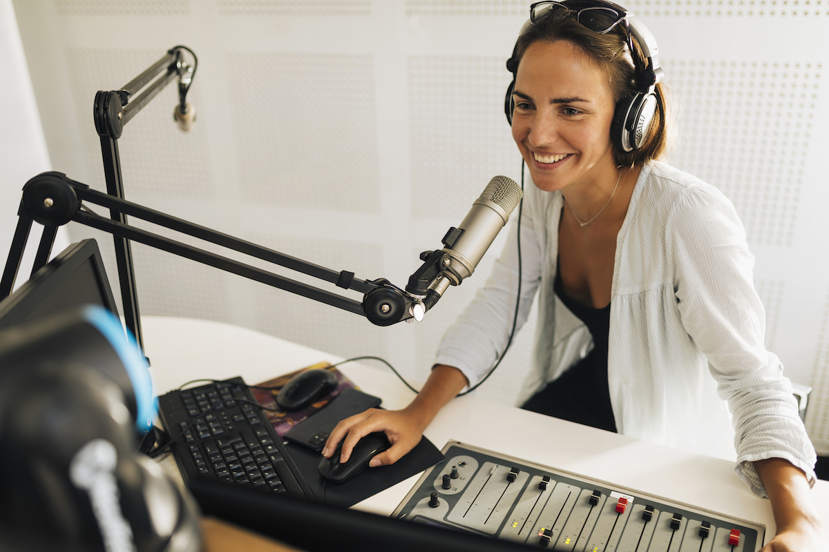 Market your podcast: image of female podcaster smiling