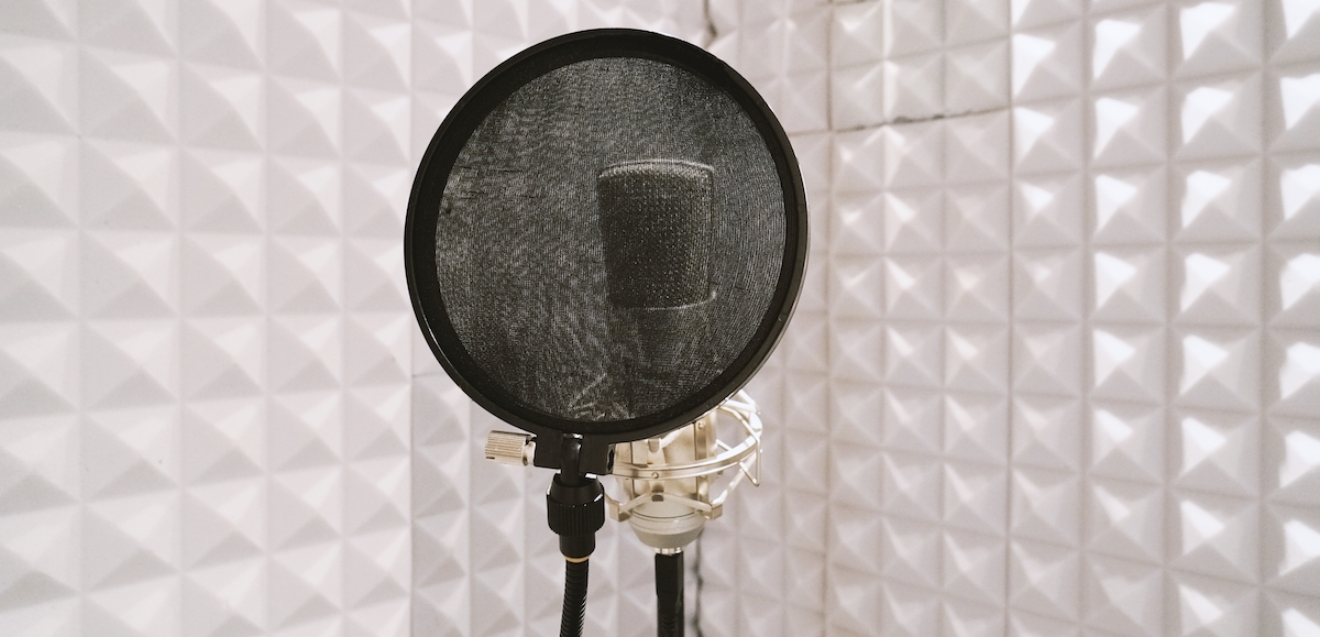 5 must-haves for a voice actor's recording environment: image of a microphone and pop filter in a soundproofed room.