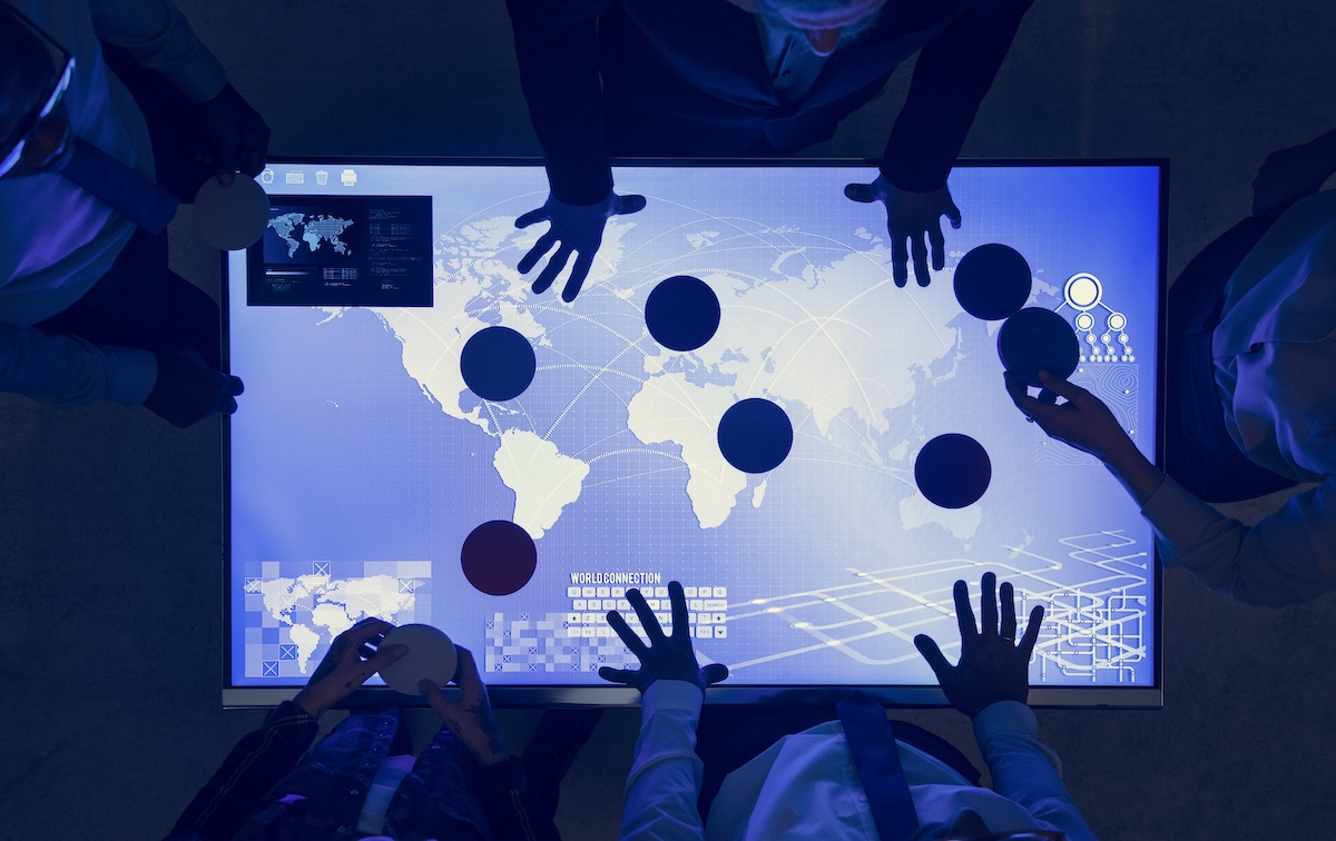 Video marketing strategy: image of people with their hands on a screen showing a global map