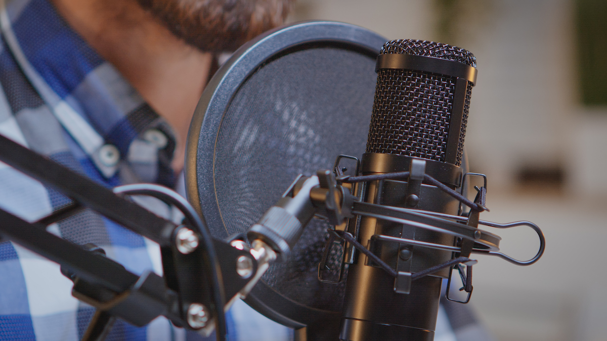 Writing to be heard: close up image of a voice actor in front of a microphone