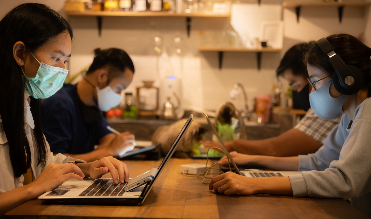 Make your business stand out: image of a group of people wearing covid masks in front of their laptops