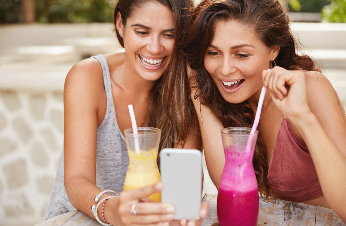 Humor in ads: image of two young women laughing at funny videos on a smartphone
