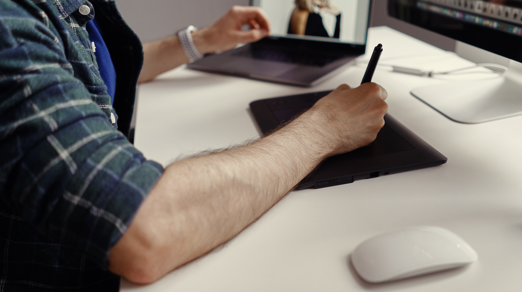 Interactive content: image of a man using a tablet and a laptop.