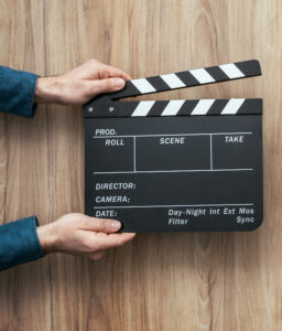 Voice actor: image of assistant holding a clapperboard in front of a camera